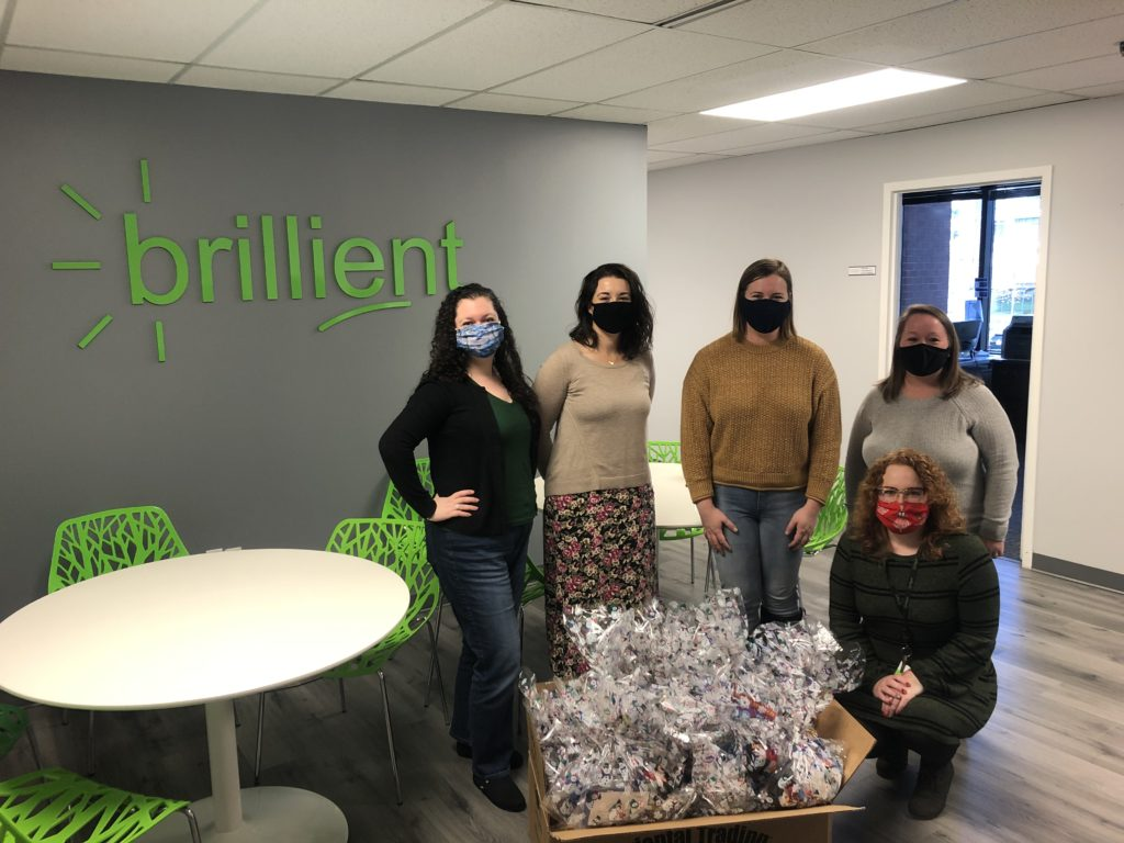 HR Team in front of the Brillient logo