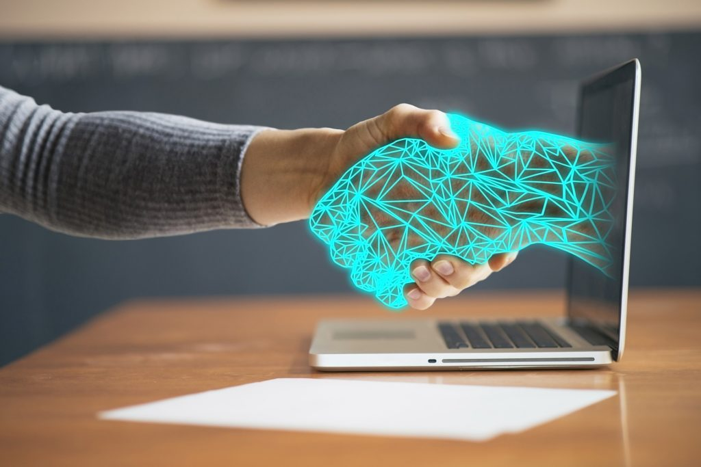 Human hand shaking a digital hand coming out of a computer screen